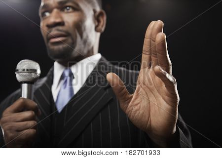 African man in suit holding microphone and gesturing