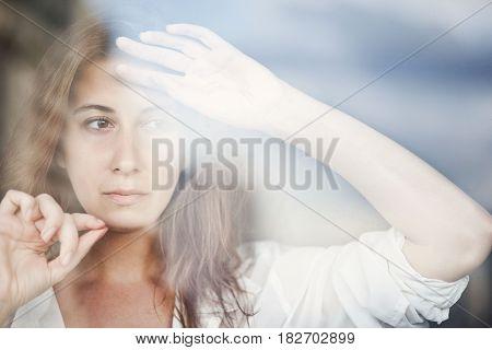 Portrait of a sad woman behind the window glass. Rainy weather