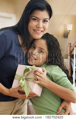 Hispanic mother hugging daughter with gift