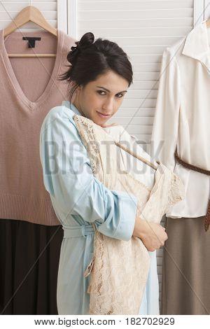 Mixed race woman holding dress