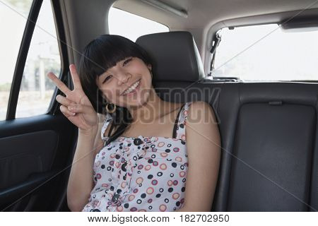 Asian woman gesturing peace sign in back seat of car