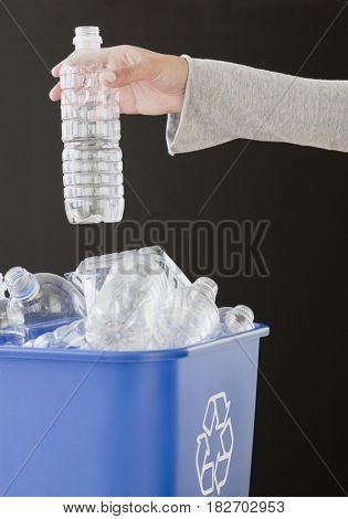 Woman recycling plastic bottle