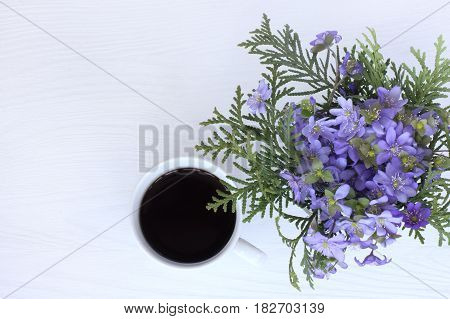 Bouquet of wild spring flowers with a cup of hot drink top view / fragrant coffee break