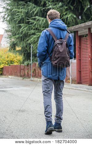 Teenage boy walking alone in city street with backpack, seen from the back
