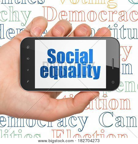 Politics concept: Hand Holding Smartphone with  blue text Social Equality on display,  Tag Cloud background, 3D rendering