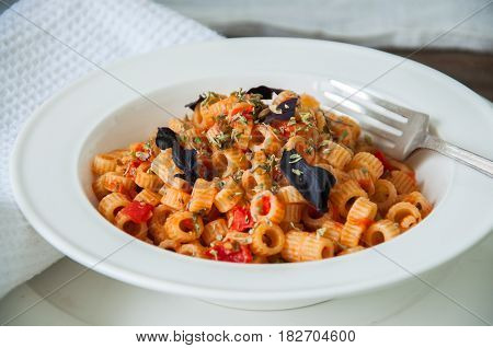 Close Up Of Tomato Sause Pasta And Basil In A White Plate.