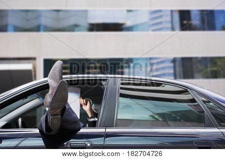 Feet of mixed race businessman sticking out car window