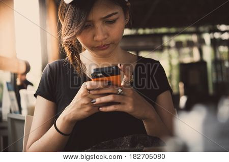 A young woman is using her smart phone while is sitting in restaurant