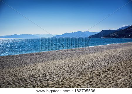 Empty sandy beach during the day under a clear blue sky