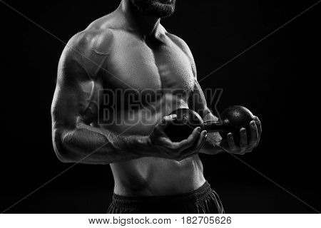 The colorless image of torso of attractive male body builder with weight on black studio background.