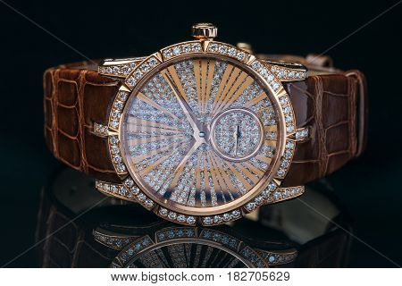 Luxury golden watch with leather strap decorated with diamonds
