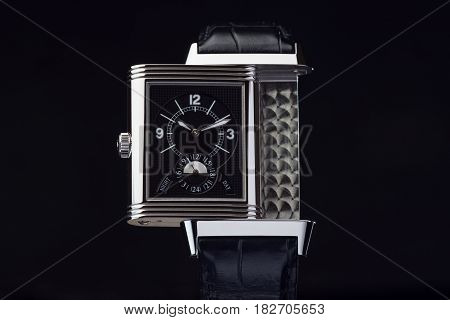 Luxury ancient wristwatch with black leather again dark background