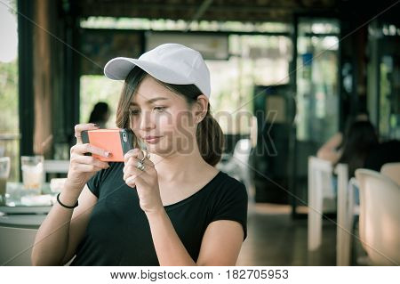 A young woman is using her smart phone while is sitting in restaurant at a table with camera