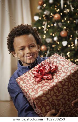 Mixed race boy holding Christmas gift