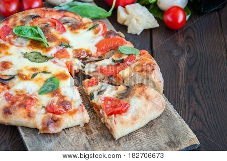 Close Up Of Pizza With Tomatoes And Mushrooms Mozarella On A Wooden Board. Raw Vegetables- Cherry To