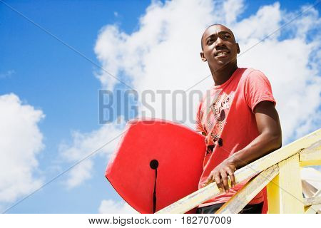 African man holding body board