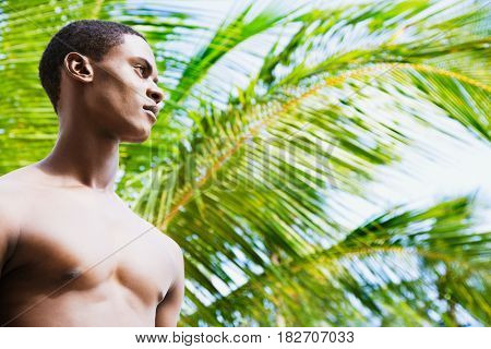 Bare chested African man in front of palm tree looking pensive