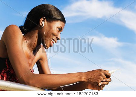 African woman wearing headphones and holding MP3 player