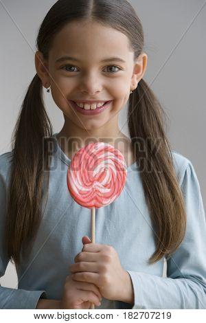 Hispanic girl holding lollipop