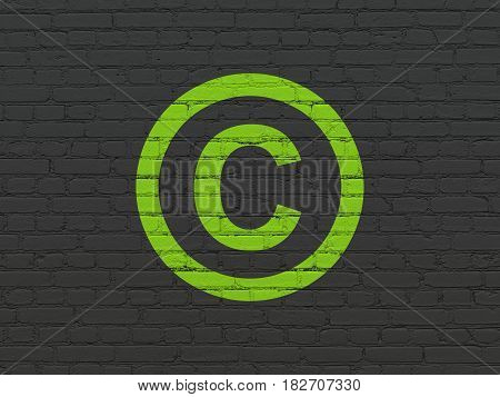 Law concept: Painted green Copyright icon on Black Brick wall background