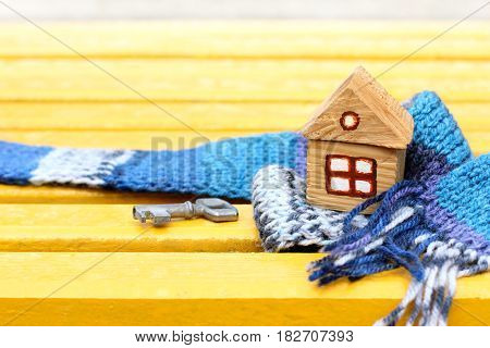 Small wooden house with a key in a warm blue scarf on a yellow surface / warming works of buildings