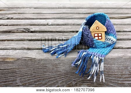 Small house in a warm scarf on a very old wooden surface / warming atmosphere for living