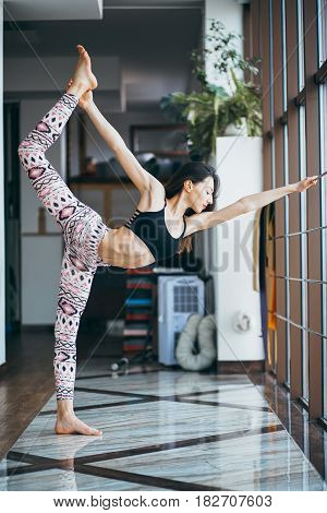 Young attractive woman practicing yoga on the floor near window at the gum