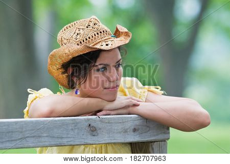 Hispanic girl leaning on fence and looking pensive