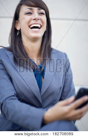 Mixed race businesswoman holding cell phone and laughing