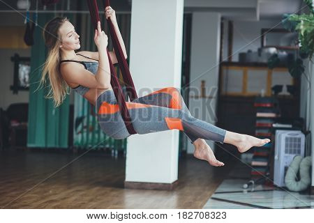 Young woman performing antigravity yoga exercise in the gym