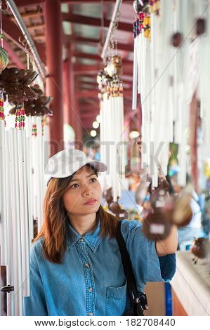 A young woman wearing a hat is walking in the market streets of an asian countryThailand