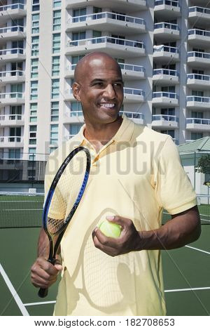 African man holding tennis ball and racket