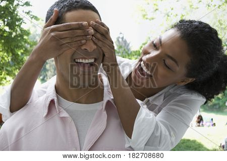 Woman covering man's eyes