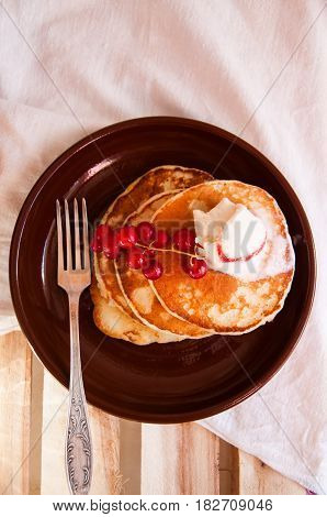 Freshly Baked Whole Wheat Flour Pancakes With Red Currant And Ice Cream In A Brown Plate On A Wooden