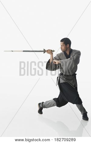 Mixed race martial artist holding sword