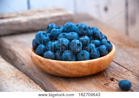 Heap Of Fresh Ripe Raw Bluberries In A Small Wooden Plate On A Wooden Background. Rustic Style And C