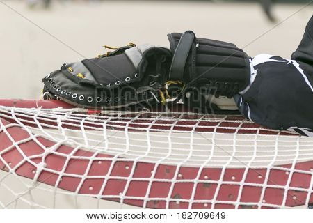 goalie resting his glove hand on the net between plays