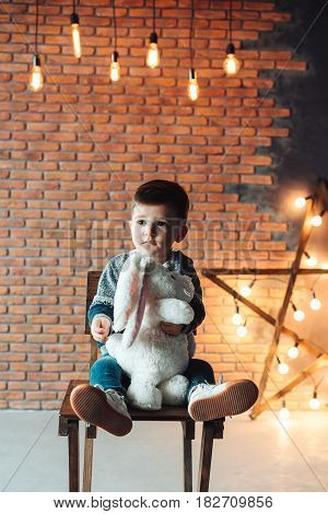 little boy sitting on a chair and holding a plush toy