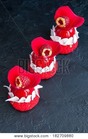 Romantic French Choux Pastry With Raspberry Mousse Cream Covered With Red Mirror Glaze And Rose Peta