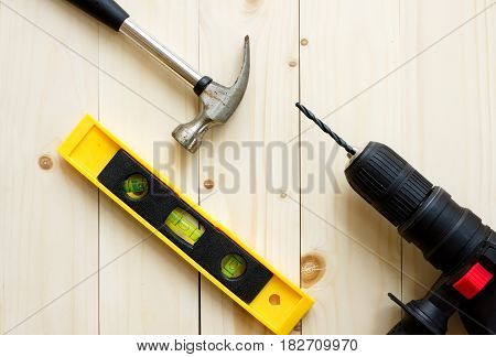 Drill hammer levels on wooden background for DIY concepts