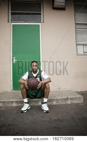 Serious African basketball player sitting with ball outside door