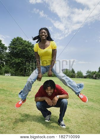 Woman leaping over man in park