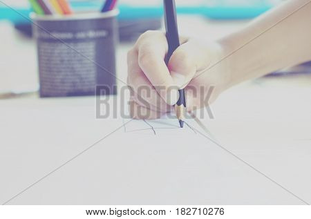 Little kid's hand drawing something on white paper. Outdoor activity learning concept for family. with wฟrm tone color effect.