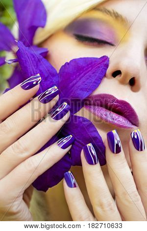 Lilac makeup and manicures with floral pattern on the nails on the woman with the Clematis.