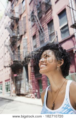Mixed race woman looking up on urban street