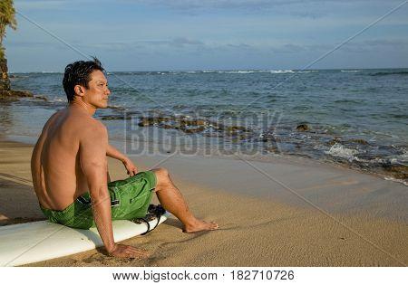 Japanese man sitting on surfboard on beach