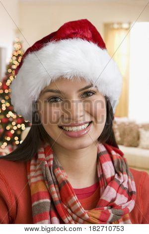 Hispanic teenage girl wearing Santa hat