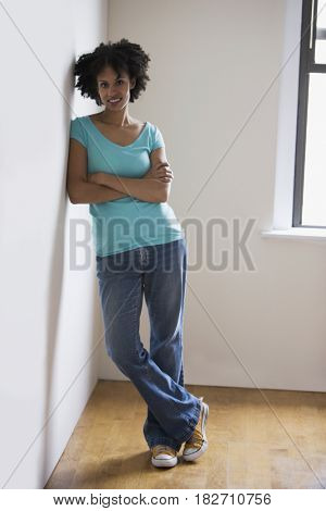 Mixed race woman leaning against wall with arms crossed