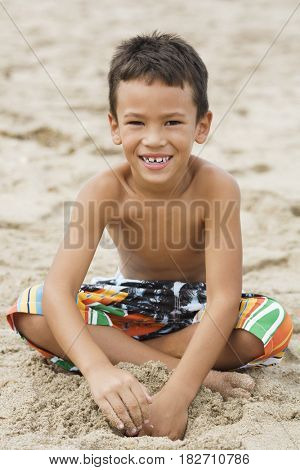 Mixed race boy in swim trunks sitting on beach
