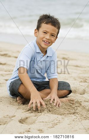 Mixed race boy playing with sand on beach
